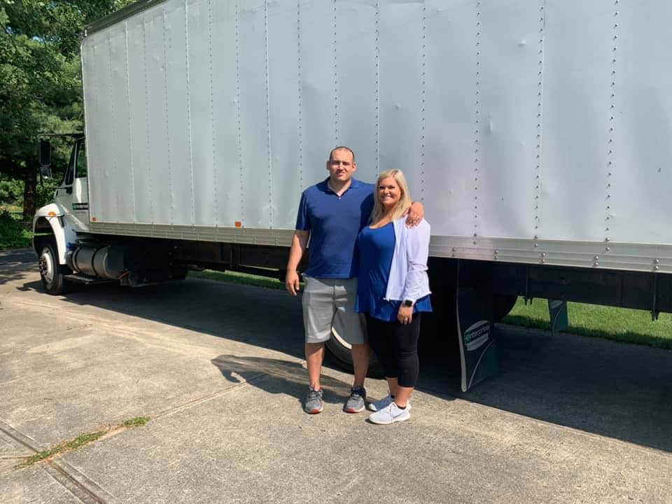 proud owners of In & Moving standing outside next to their moving truck